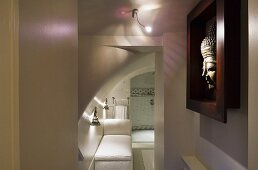 A play of coloured light and shadow in a bathroom and a Buddha head in a dark red frame