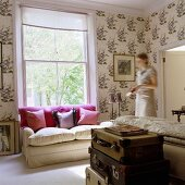 A stack of trunks, a light upholstered sofa with cushions in front of a window, patterned wallpaper and a woman in the room