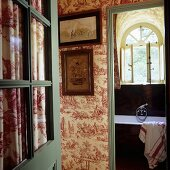 An open door with a view into a hallway and a bathroom in a French country house