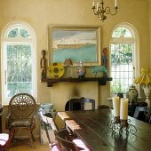 A dining table in front of a fireplace with African art on the mantelpiece and windows with round arches in a country house-style living room