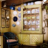 A blue wicker chair and a plates hung on the wall next to a crockery cupboard