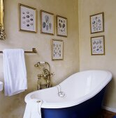 An old fashioned bathtub with brass taps and a collection on pictures on a yellow-painted wall