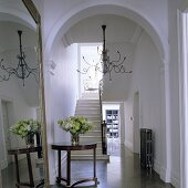 An arched doorway in an elegant hallway with a view of a stairway, an antique side table and a chandelier with Medusa-like arms