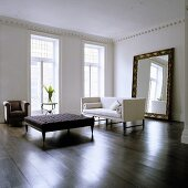 A minimalistic living room in a period building with a coffee table and a white sofa in front of a free-standing mirror