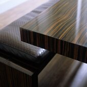 A veneered table made of tropical wood and a bench upholstered in leather