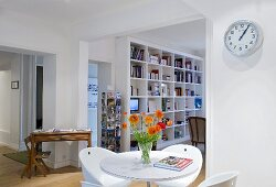 Bistro table and chairs with a view through a doorway to built-in shelves