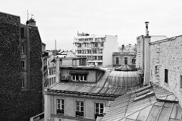 A black and white photo of a roofscape in Paris