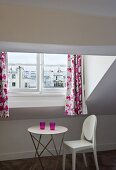 An occasional table and a chair under a slopping roof and patterned curtains at the window