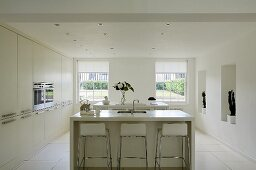 A free-standing kitchen counter with bar stools in the centre of a white kitchen