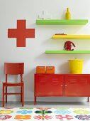 A collection of small, colourful items of furniture on and against the wall