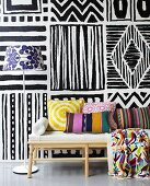 Colours contrasting with black and white - cushions on an upholstered bench in from of a painted wall