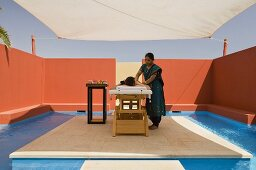 A massage being performed under the Mediterranean sky - a woman being treated under a sunshade and surrounded by a red wall