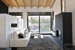 A designer living room with a view of the garden - a leather sofa in front of a partition wall in front of a black fireplace