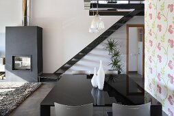 An open living-room-cum-dining-room with a black shiny table in front of a flight of stairs and a fireplace