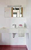 A corner of a bathroom - a designer washstand with a mirror and lights
