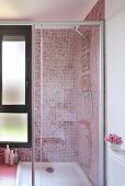 A bathroom with a glazed shower unit and red mosaic tiles