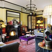 A brightly coloured living room with a fireplace, upholstered furniture and a wrought iron chandelier