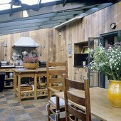 An open-plan kitchen with wood panelled ceilings in a conservatory