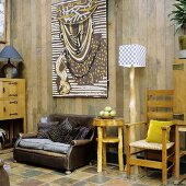 A rustic room with a leather armchair and handmade furniture in front of a wooden wall