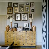 An old apothecary chest of drawers with a collection of photos hanging on the wall above it