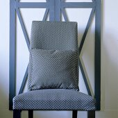 An upholstered chair with a matching cushion