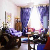 A living room with upholstered furniture and purple curtains at the window