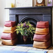 Two sets of colourful sisal baskets and a vase of flowers in front of a dark wood panelled fireplace
