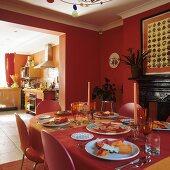Ziegelrotes Esszimmer mit gedecktem Tisch und Blick auf Durchgang und offene Küche