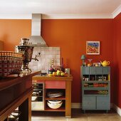 A kitchen in a country house with orange-painted walls and kitchen furnitures with a stainless steel extractor fan