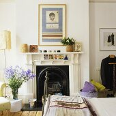 A fireplace with a white mantelpiece in a bedroom
