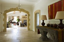 An anteroom with an antique Greek stone table and a rounded archway with a view into a living room