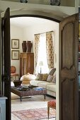 A view through an open wooden double door of a coffee table and an upholstered sofa