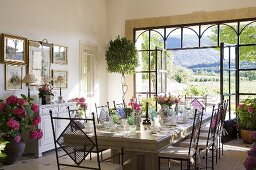 A Mediterranean dining room with a large laid table and open terrace doors with a view
