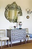 A mirror hanging above an antique chest of drawers with Rococo chairs standing against the wall in a hallway