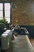 A rustic dining room with a brick wall and a kitchen counter with storage jars