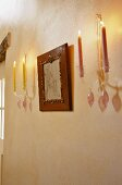 Wall mounted candle stick with coloured burning candles either side of a framed picture