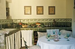 A country house kitchen - wine glasses on a table in front of a green-tiled kitchen counter and close curtains in front of cupboards