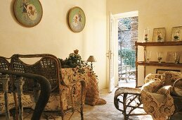 Wicker furniture with cushions and a wall shelf with vases in a country house-style living room and a view through an open garden door