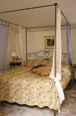 A bedroom with a tiled floor and metal four poster bed with a patterned cover in a Mediterranean country house