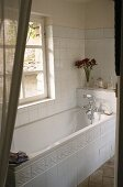 A view of a white tiled bathroom with a bathtub and a view of the garden
