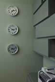 Clocks on a grey wall showing different times