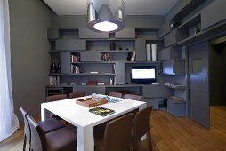 A designer living room in grey - a white table and metal lampshades in front of a wall with built-in shelving