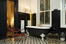 A bathroom with black wall panelling in a mixture of styles - metal furniture on black and white tiles