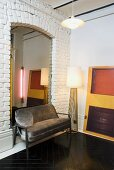 An upholstered bench and a floor lamp against a white brick wall and a mirror in a niche