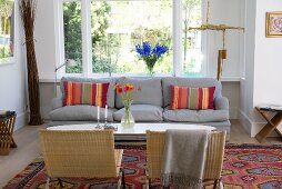 Wicker chairs and gray sofa around an oval coffee table in front of a floor to ceiling window