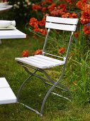 White folding chair in a garden with red flowers