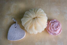 A heart-shaped pumice stone with a yellow bath sponge and a bar of rose soap
