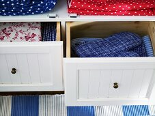 Pads and patterned fabric in drawers with white wooden fronts