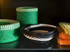 Green basket set next to black and white patterned wicker bowls on a black surface
