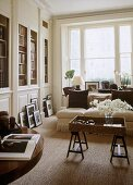 A traditional, neutral sitting room with plain window, built in bookcases, upholstered sofa, wooden tray on trestle legs